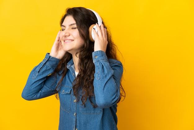 Garota russa adolescente isolada em um fundo amarelo ouvindo música e cantando