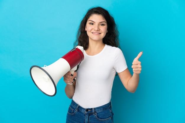 Garota russa adolescente isolada em um fundo azul segurando um megafone com o polegar para cima