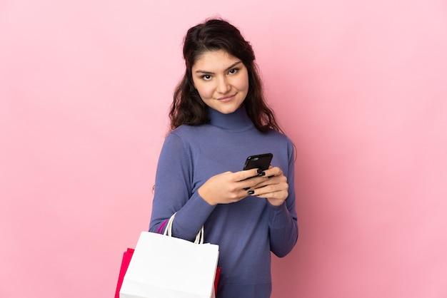 Garota russa adolescente isolada em um fundo rosa segurando sacolas de compras e escrevendo uma mensagem com seu telefone celular para uma amiga
