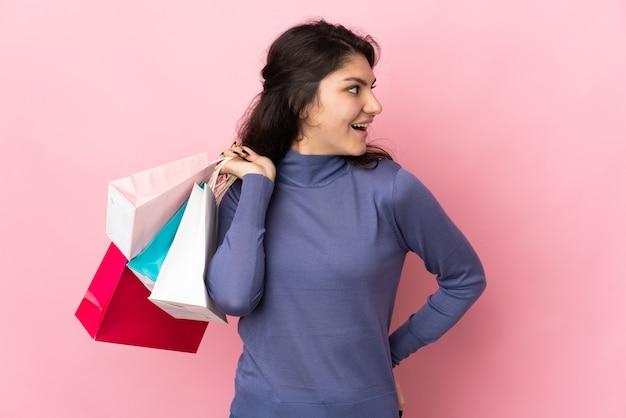 Garota russa adolescente isolada em um fundo rosa segurando sacolas de compras e olhando para trás