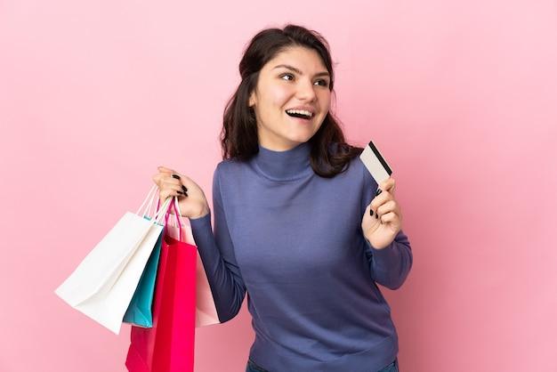 Garota russa adolescente isolada em um fundo rosa segurando sacolas de compras e um cartão de crédito