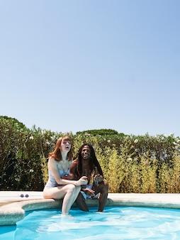 Garota russa com cabelo ruivo e garoto afro-americano com dreadlocks bebendo algumas cervejas sentadas na beira da piscina