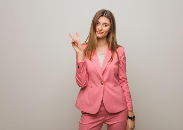 Garota russa de negócios jovem, fazendo um gesto de vitória