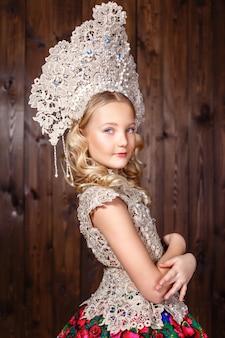 Garota russa em um vestido folclórico russo sobre fundo de madeira