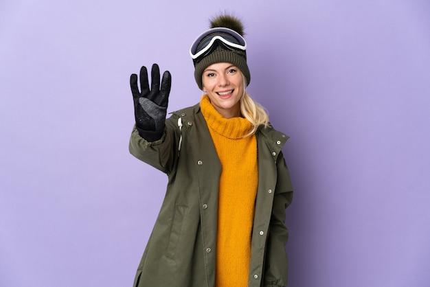 Garota russa esquiadora com óculos de snowboard isolados em um fundo roxo feliz e contando quatro com os dedos