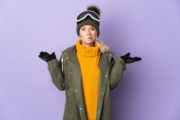 Garota russa esquiadora com óculos de snowboard isolados na parede roxa, tendo dúvidas ao levantar as mãos