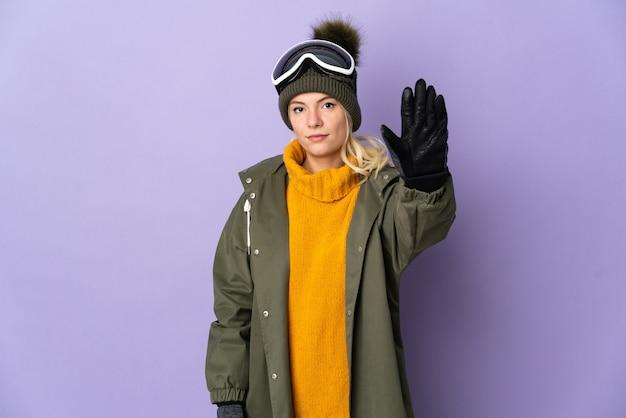 Garota russa esquiadora com óculos de snowboard isolados no fundo roxo fazendo gesto de pare