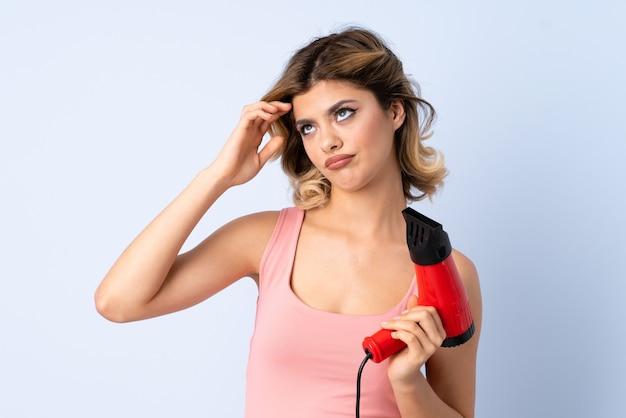 Garota russa segurando um secador de cabelo isolado no azul, tendo dúvidas e confusa expressão facial