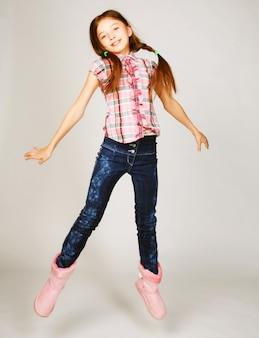 Garota salta sobre um fundo cinza