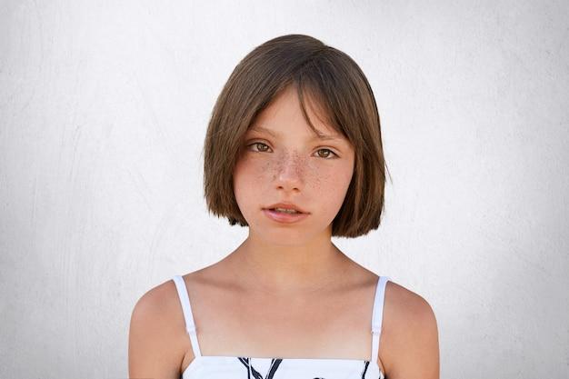 Garota sardenta séria, com cabelos cortados e olhos escuros, olhando diretamente para a câmera, isolada no branco. menina adorável elegante vestido branco. pessoas, infância, conceito de emoções