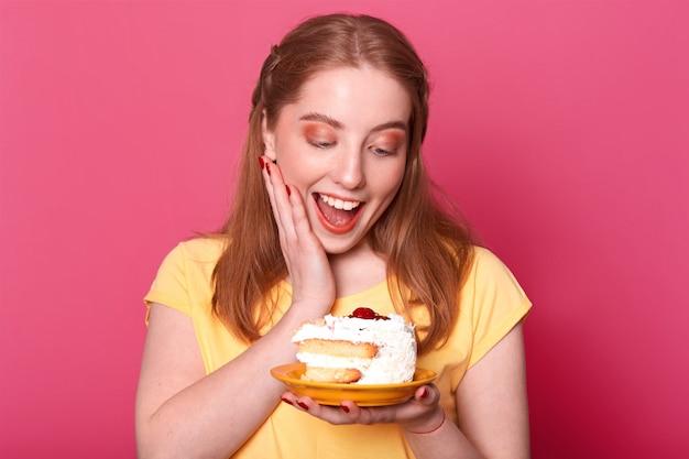 Garota satisfeita satisfeita com cabelos castanhos claros, segura um pedaço enorme de bolo saboroso, mantém a boca aberta, cheia de prazer, vestida com camiseta amarela casual
