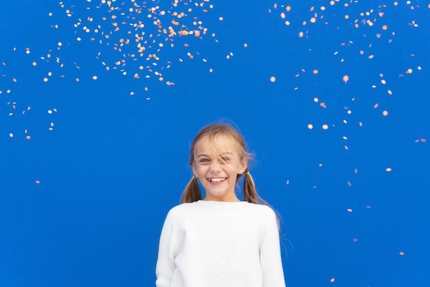 Garota satisfeita sorrindo em um confete voador