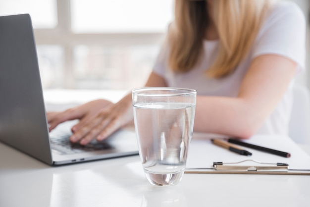 Garota saudável usando laptop com copo de água