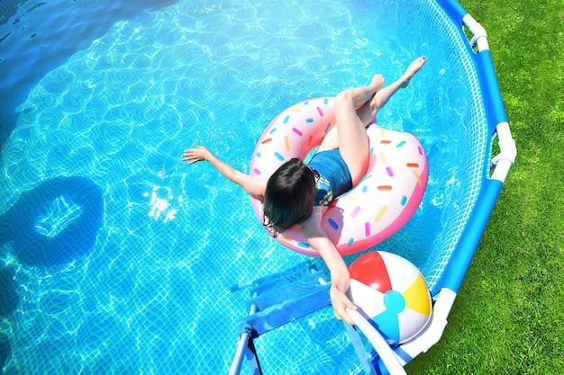 Garota se diverte em uma piscina de estrutura metálica de verão.