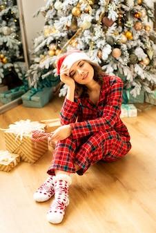 Garota se divertindo e comemorando o natal. no fundo decorou a árvore de natal com presentes.