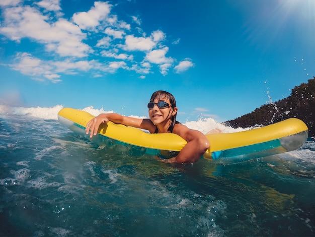 Garota se divertindo flutuando no colchão de ar no mar