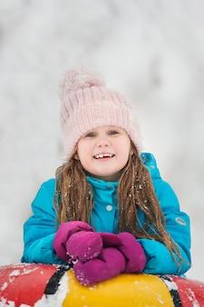 Garota se divertindo no tubo de neve. garota está montando um tubo.