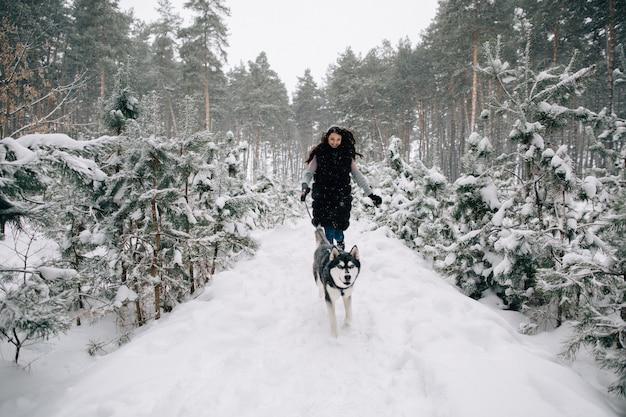 Garota se divertir com seu cachorro husky na floresta de pinheiros de inverno nevado
