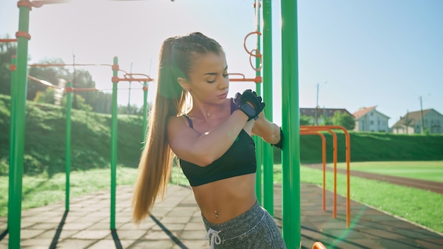 Garota se espreguiçando no campo de esportes pela manhã