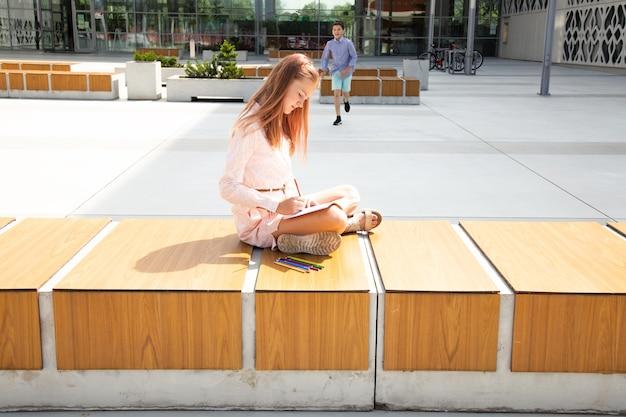Garota se senta no banco e lê um livro na porta da escola, perto do prédio da escola. estudante está correndo em direção a ela no fundo