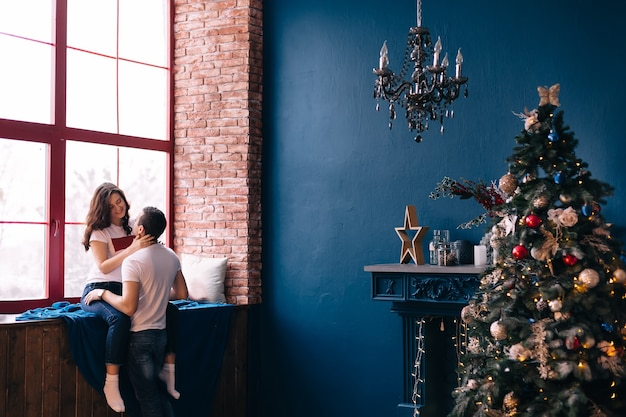 Garota se senta no parapeito da janela e abraça o cara. sala aconchegante com lareira e árvore de natal.