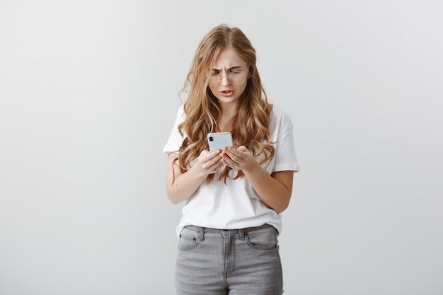 Garota se sentindo estranha ao enviar mensagem para o número errado. retrato de uma jovem atraente com problemas de óculos, xingando enquanto franzia a testa e parecendo incomodado com a tela do smartphone, navegando na rede