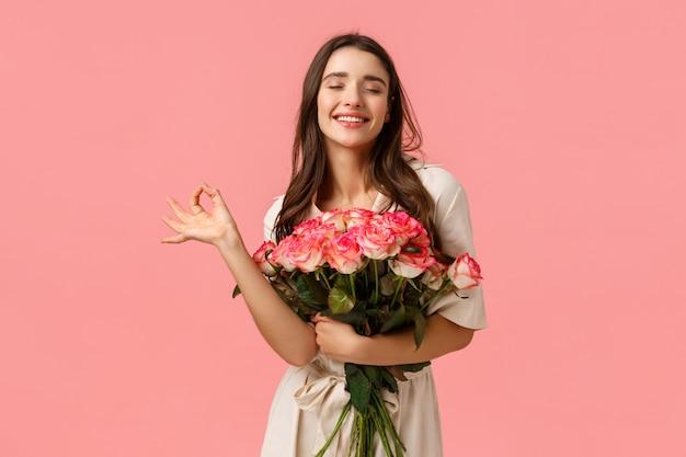 Garota se sentindo incrível, namorado amá-la como rainha. encantadora e elegante fêmea morena de vestido, segurando rosas, fechar os olhos e sorrindo encantada, ficou o buquê de flores perfeito, parede rosa