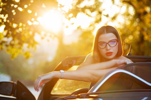 Garota sedutora de óculos, sentada em um carro conversível com luz do sol dourada da noite. espaço para texto