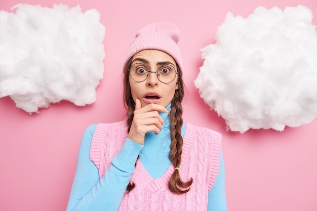 Garota segura o queixo, sem fala, dentro de casa usa óculos redondos transparentes roupas casuais reage a novas poses incríveis contra rosados