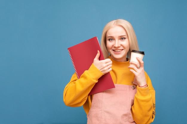 Garota segura uma xícara de café e um caderno nas mãos, olha para a câmera e sorri, isolado no azul