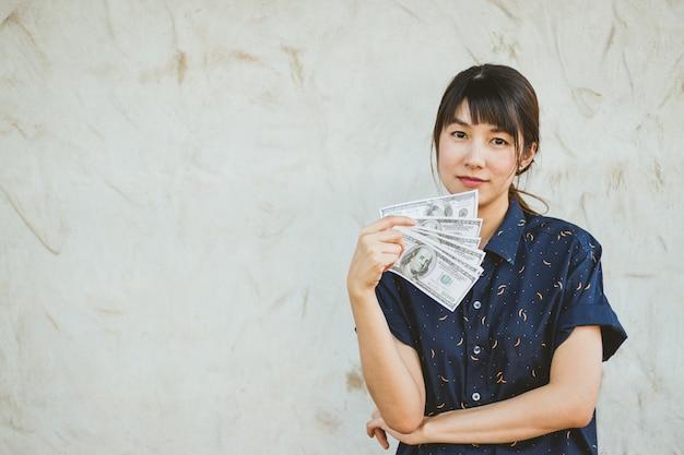 Garota segurando muitos nós notas de dólar sorrisos