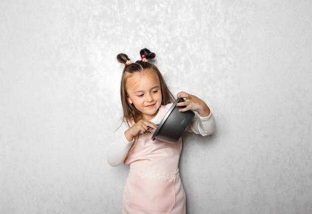 Garota segurando uma grande farinha de chicote, fazendo panquecas sozinha