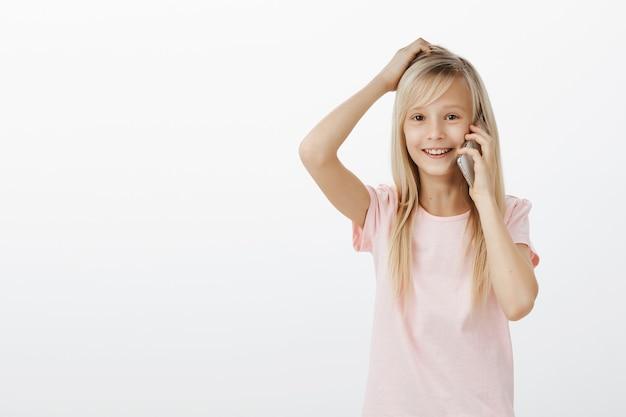 Garota sem noção, sem saber como responder. filha adorável confusa em uma camiseta rosa, coçando a cabeça e sorrindo alegremente enquanto fala no smartphone, questionada e inconsciente
