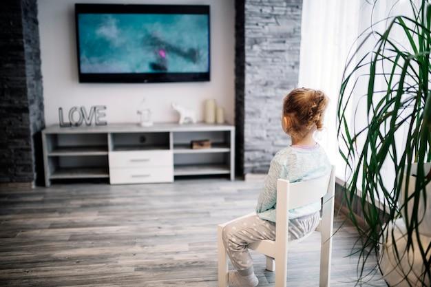 Garota sem rosto assistindo tv