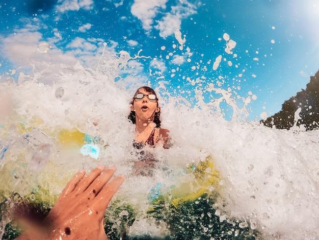 Garota sendo espirrada pelas grandes ondas