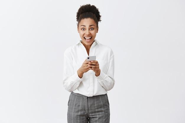Garota sendo oprimida e animada lendo oferta incrível recebida pela internet, verificando a caixa de correio no smartphone, olhando maravilhada, em pé sobre uma parede cinza em um terno