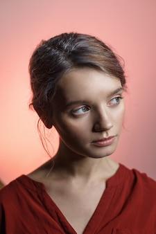 Garota sensual caucasiano atraente na camisa vermelha, olhando para longe e inclinando a cabeça dela. retrato da beleza no fundo rosa