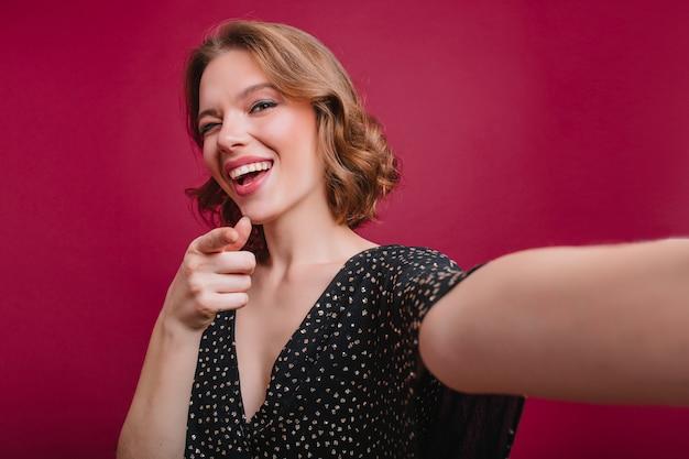 Garota sensual com tatuagem bonita no braço fazendo selfie mulher encaracolada de cabelos curtos em vestido preto tirando foto de si mesma na sala com interior roxo.