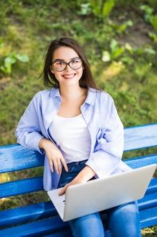 Garota senta no banco do parque e usa seu laptop
