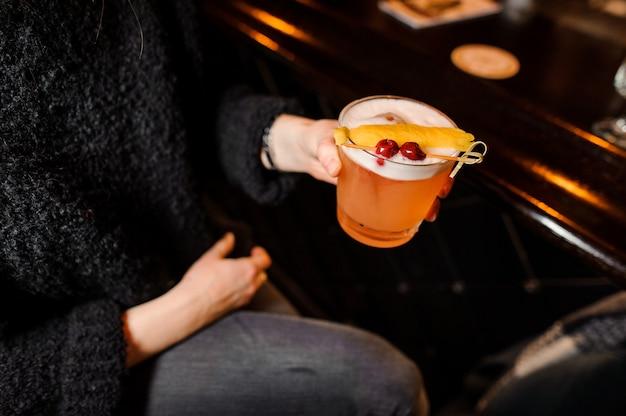 Garota senta-se em um balcão de bar e mantém um cocktail alcoólico de laranja na mistura azeda