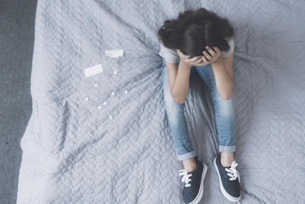 Garota senta-se na cama com a cabeça descansando em suas mãos