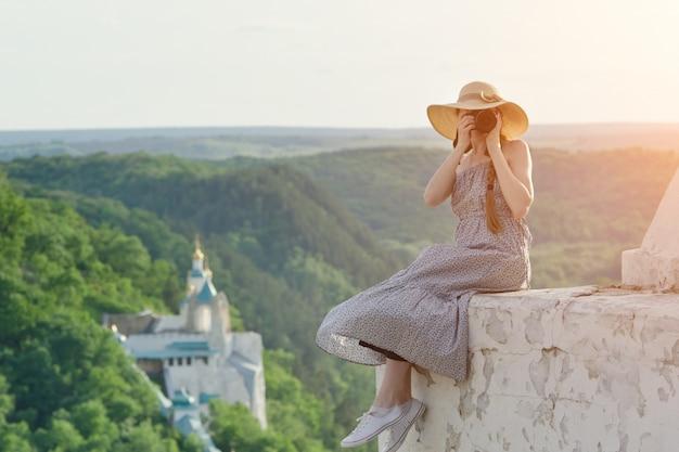Garota senta-se na colina com câmera. floresta e templo abaixo