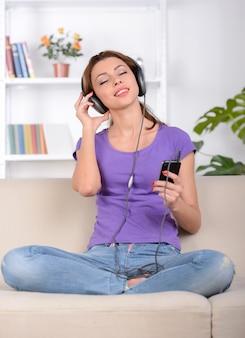 Garota senta-se no sofá em posição de lótus e ouve música.