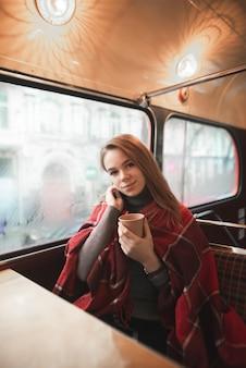 Garota sentada em um café perto da janela com uma xícara de café nas mãos, coberta com um cobertor para aquecer em um dia frio de inverno