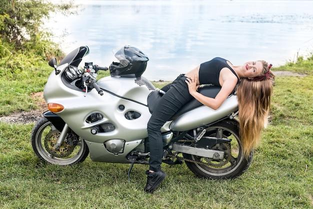 Garota sentada em uma moto esportiva no fundo do lago