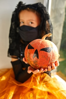 Garota sentada na janela em casa com fantasia de halloween com abóbora jack ou laurent, criança usando máscara preta protegendo contra coronavírus, halloween em quarentena
