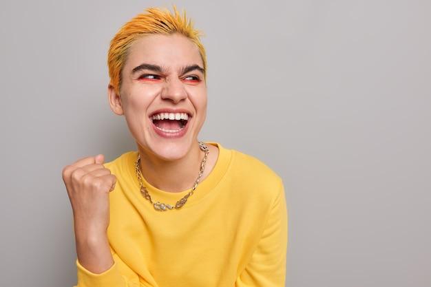 Garota sente que o vencedor comemora o sucesso aperta o punho parece feliz e usa um macacão amarelo casual no espaço cinza em branco pertence à subcultura jovem
