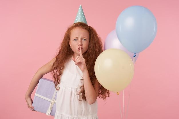 Garota séria com cabelo encaracolado sexy em roupas festivas em pé sobre um fundo rosa e balões coloridos, segurando uma caixa embrulhada para presente e pedindo para manter o silêncio com o dedo indicador levantado nos lábios