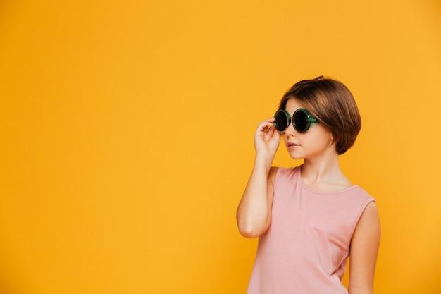 Garota séria confiante em óculos de sol, olhando de lado