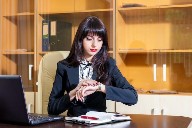 Garota séria no escritório olhando para o relógio